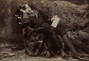 Wilde in velvet and furs reclining on a sofa in elaborate studio interior. Photograph by Sarony, circa 1882.