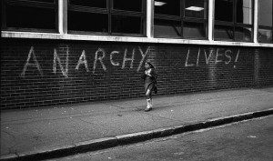 Small girl walks past the graffiti 'Anarchy Lives!'  Photo by Judy Greenway. East London, 1970s.
