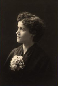 Head and shoulders portrait of Voltairine de Cleyre in 1901, wearing flowers.