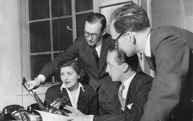 Eagle Editorial Meeting. Left to right: Ellen Vincent, assistant editor; Macdonald Hastings, Eagle 'Special Investigator'; Marcus Morris, the editor; and Michael Gibson, art editor. A version of this photo appeared in the April 9, 1954 issue.
