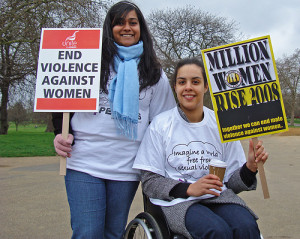 Two young women, one in a wheelchair, on International Women's Day demonstration, London 2008. Teir placards and slogans include 'End violence against women', 'Imagine a world free of sexual violence' and 'Million Women Rise 2008'.