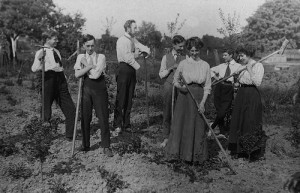 Men and women in a rural setting pose with rakes and hoes on a farming holiday in an English utopian community, probably around 1910.