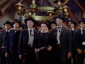 Medium shot of Emma standing in the middle of the mob of townspeople inside the saloon. They are all dressed in dark clothing.