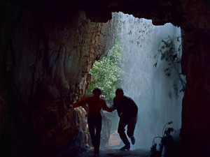 Emma and Johnny, silhouetted against the exit of a cave, pass through the waterfall into another space.