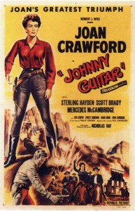 Film poster. Joan Crawford in Johnny Guitar. (Source: Wikipedia). Giant figure of Crawford in masculine clothing, reaching for her gun, towers over other figures from the cast.