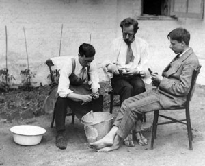 Three men peeling potatoes in garden, around 1917.