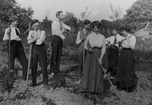 On a farming holiday in an English utopian community, probably around 1910. Men and women pose with rakes and hoes.