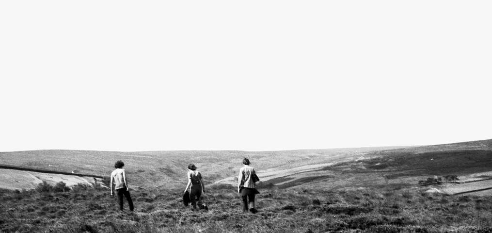 London anarchists in Yorkshire, 1970s. Photograph of three young people walking across moorland towards the horizon.