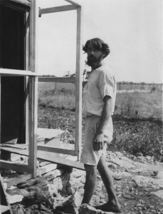 'Raymond the carpenter', barefoot, stands outside a building under construction at Whiteway.