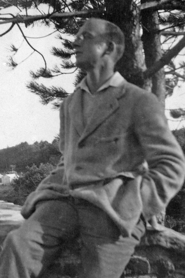 Wilfrid Gibson, in the countryside, casually dressed in open-necked shirt and what may be the home-made suit. He is gazing into the distance in 'Great Poet' mode.